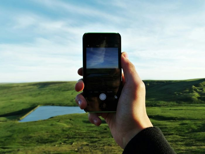 Cropped Hand Photographing Green Landscape With Smart Phone