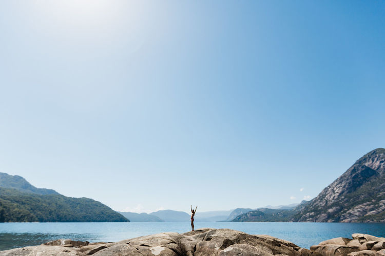 Man standing on shore by sea against clear sky