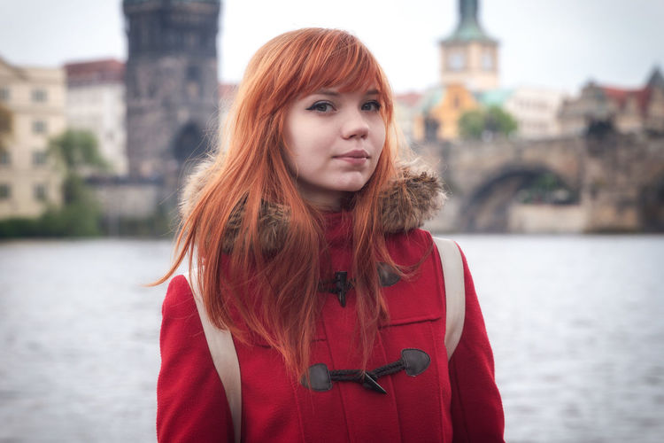 Portrait Of Young Woman Standing Against River In City