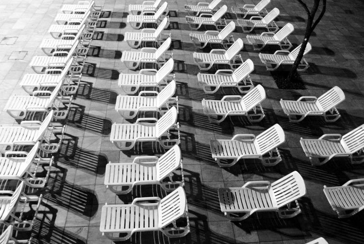 High angle view of empty chairs in row on promenade