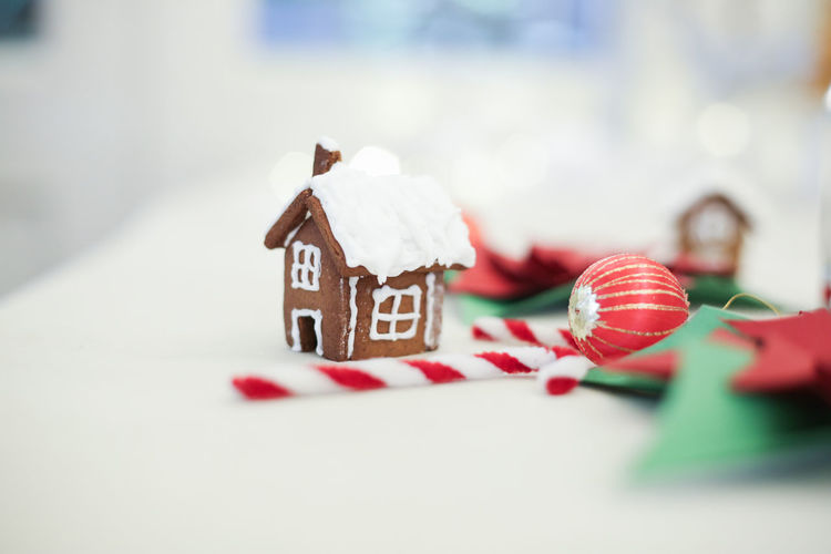 Close-up of gingerbread house and white mugs decorated on table during christmas
