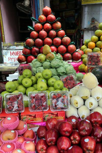 Street trader sell fruits outdoor on February 11, 2014 in Kolkata India. Apple Assortment Bazaar Buisness Calcutta City Customer  Food Freshness Fruit Greengrocery Grocery Healthy Eating India Kolkata Market Market Stall Marketplace Melon Pomegranate Sale Seller Shop STAND Street