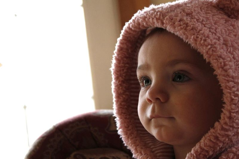 Cute baby girl in knit hat at home
