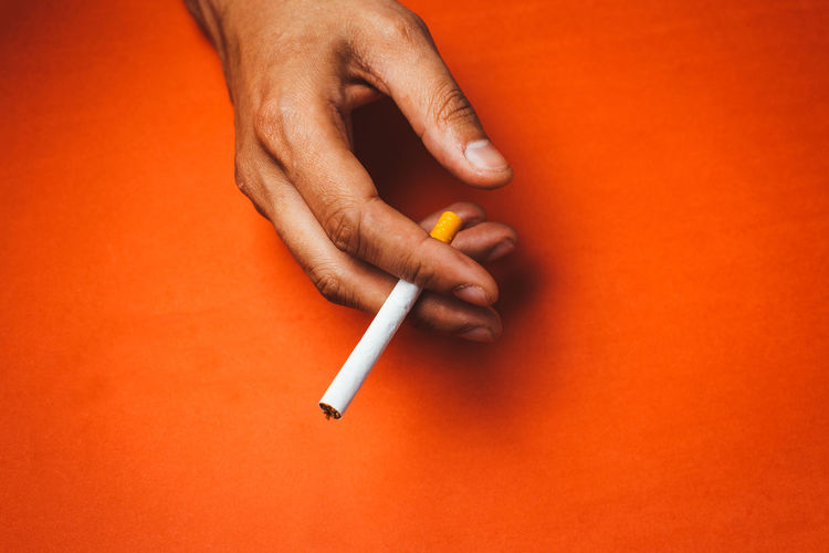 Cropped hand holding cigarette against orange background