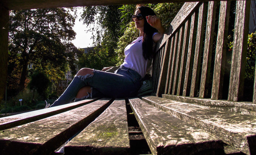 Sunny Day Brunette Wooden Bench In Garden One Woman Only Beautiful Woman Bench Seat Sitting Outside Sitting Alone Sitting Pretty From My Point Of View Full Length Sunlight Casual Clothing Handstand