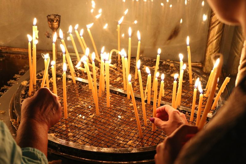 Cropped image of hands placing illuminated candles on metal grate at church