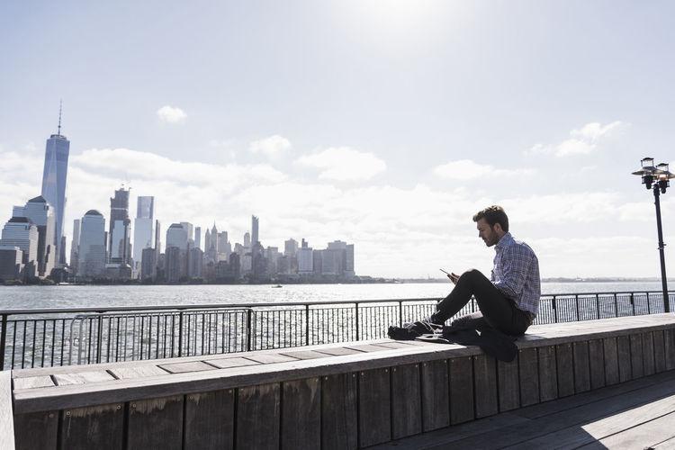 Man sitting on railing against modern buildings in city
