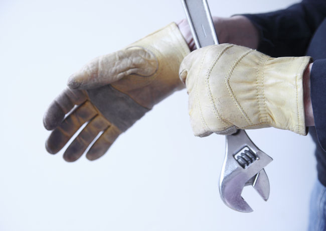 Workman with tool pulls on gloves Blue Collar Worker Casual Clothing Close-up Copy Space Fingers Hands Handyman Holding Man Protective Workwear Tool Trade White Background Work Gloves Worker Workman