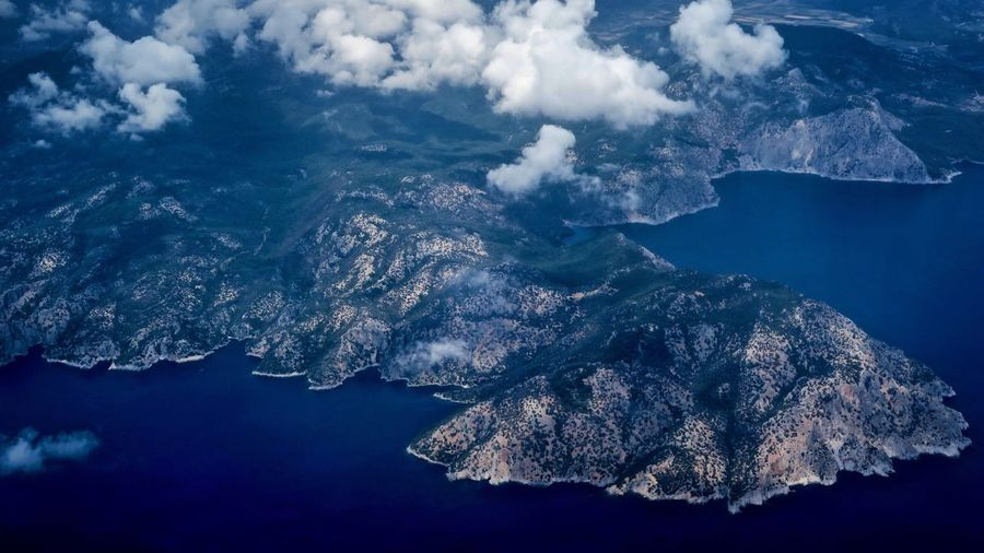 Aerial view of sea and mountains against sky