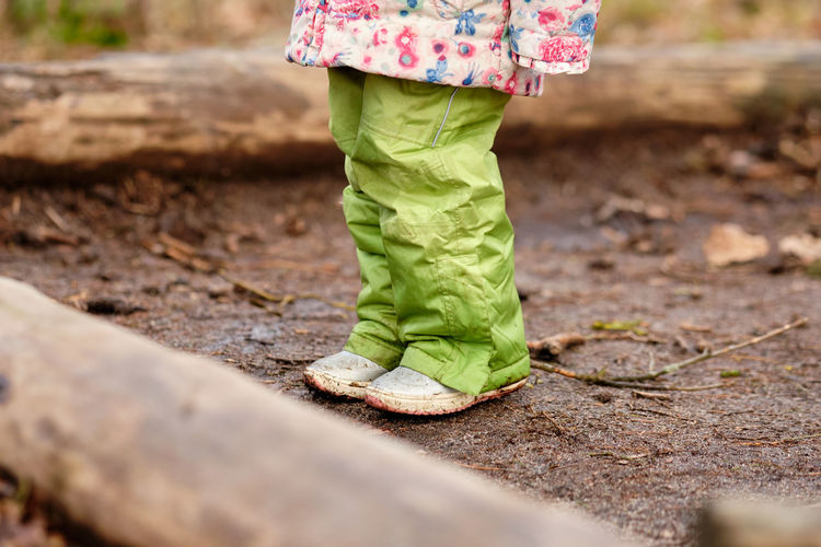 Low section of girl standing on wet field