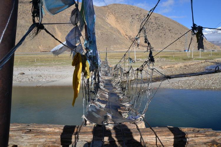Tibet Suspension Bridge Buddhism Outdoors Rope Shadow Sunlight Suspension Bridge Tibet Life Transportation Water Wood - Material Wooden Post
