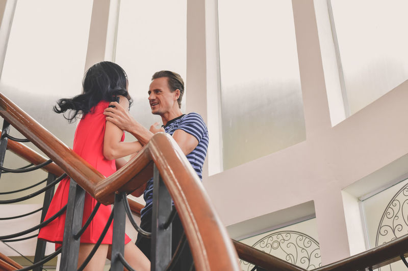 Low angle view of father scolding daughter while standing on staircase at home