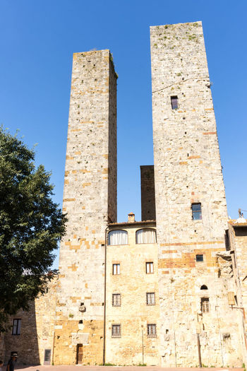 The towers in San Giminano, Italy San Gimignano Tuscany Architecture Blue Building Building Exterior Built Structure City Clear Sky Day History Italy Low Angle View Nature No People Old Outdoors Plant Sky Sunlight Tall - High The Past Tourism Tower Tree