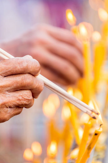 People are lighting incense stick to pray for goodness Buddhism; Burn; Candle; Close-up Culture; Day Fire Focus On Foreground Goodness; Holding Human Body Part Human Hand Incense-sticks; Incense; Merit; Mist; One Man Only One Person Outdoors People Pray; Religion; Smell; Smoke; Tradition;