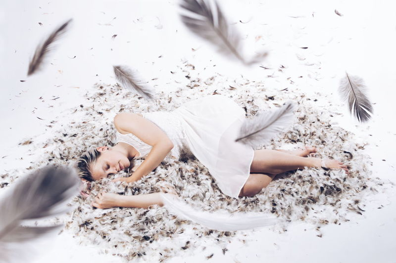 High angle view of woman lying on feathers over white background
