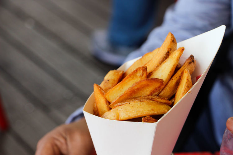 Cropped Image Of Person Holding French Fries