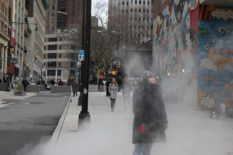 Young woman standing in rising steam in an urban environment Winter Coat Woman Heat Steam City Architecture Building Exterior Street Built Structure Walking City Street City Life Transportation Real People Incidental People Road One Person Lifestyles Motion Outdoors