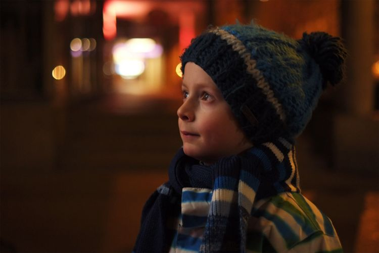 City lights with a smile. Real People Warm Clothing One Person Childhood Looking Away Night Illuminated Focus On Foreground Knit Hat Portrait Close-up Winter Headshot Outdoors People Leisure Activity Authentic Moments Lifestyles City City Life Cityscape