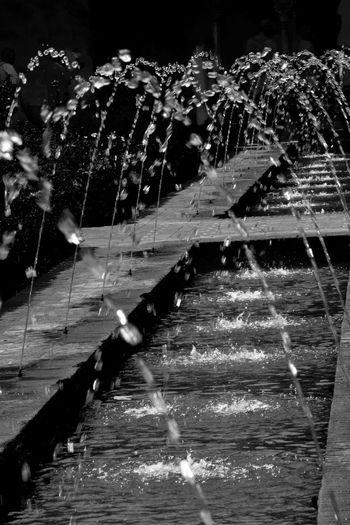 Water splashing in fountain at night