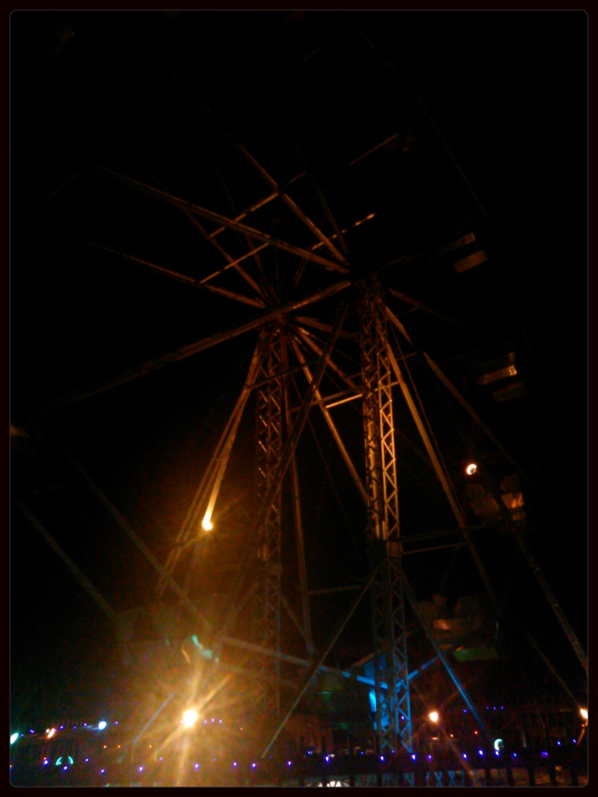 night, illuminated, low angle view, arts culture and entertainment, built structure, sky, architecture, amusement park, ferris wheel, amusement park ride, lighting equipment, outdoors, no people, transfer print, glowing, city, building exterior, celebration, clear sky, auto post production filter