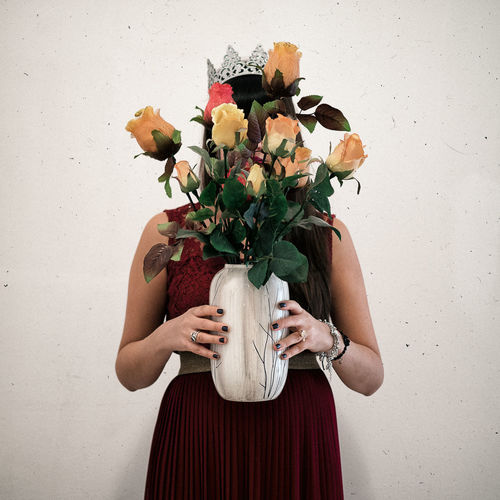 Woman Holding Flower Vase While Standing Against Wall