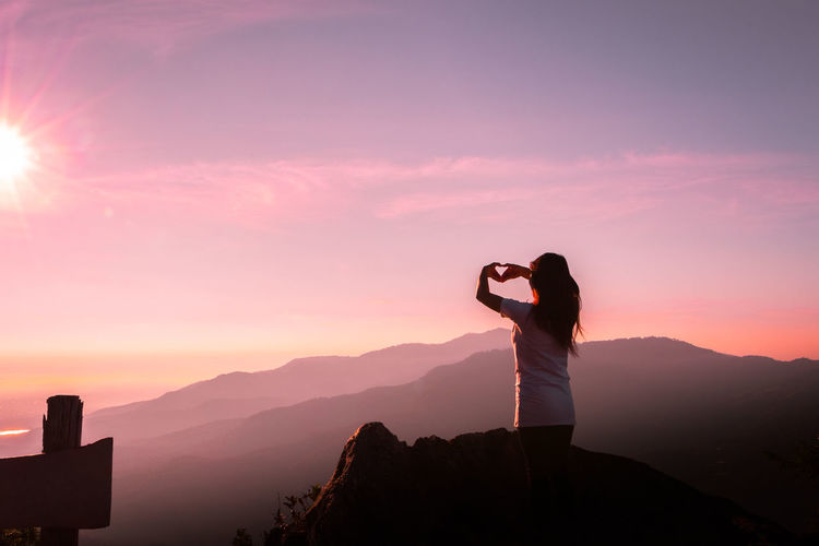 Rear View Of Woman On Mountain Making Heart Shape Against Sky During Sunset