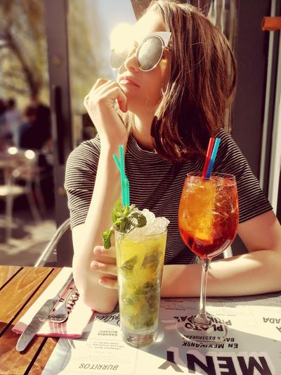 Girl sitting with drinks at table in restaurant
