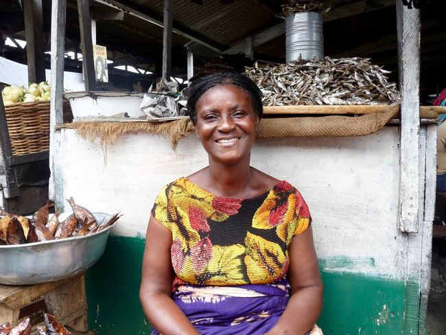 Faces Of Africa Ghana Makola Market Woman Adult Africa Cheerful Emotion Fish Food Hairstyle Happiness Market Stall One Person Portrait Real People Selling Fish Selling Food Smiling Teeth Toothy Smile Vendor Waist Up Woman Portrait Happiness Women Retail  Occupation Business Looking At Camera