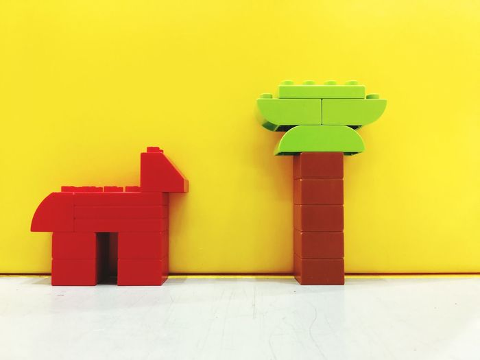 Close-Up Of Plastic Toys On Floor Against Yellow Wall