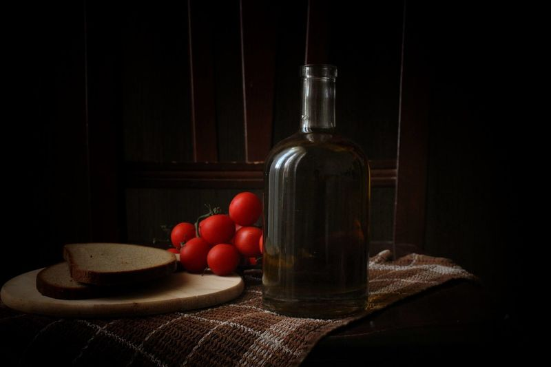 Close-up of fruits and bottle on table against black background