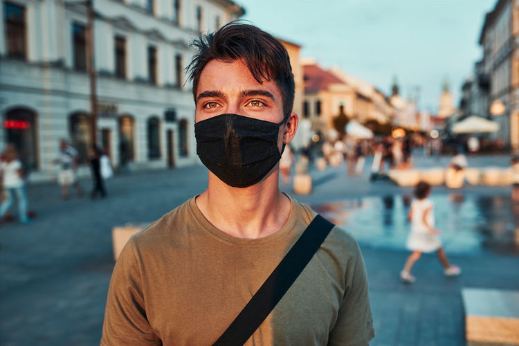 Close-up of man wearing mask looking away while standing on street in city