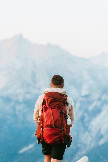 Rear view of man walking against mountain