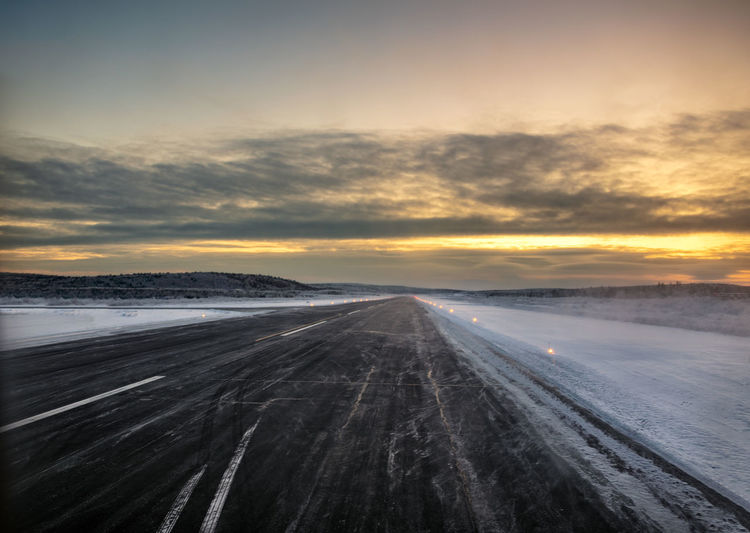 Airport runway in the Far North at dawn surrounded by snow Airtravel FAR AWAY Off The Beaten Track Airport Airport Runway Cloud - Sky Cold Temperature Dawn Environment No People Off The Beaten Path Sky Snow Sunset Transportation Travel Travel Destinations Winter