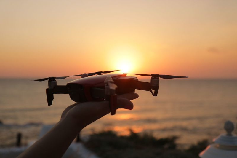 Cropped hand of woman holding drone at beach against sky