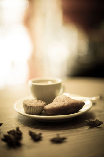 Close-up of coffee cup with cupcake on table