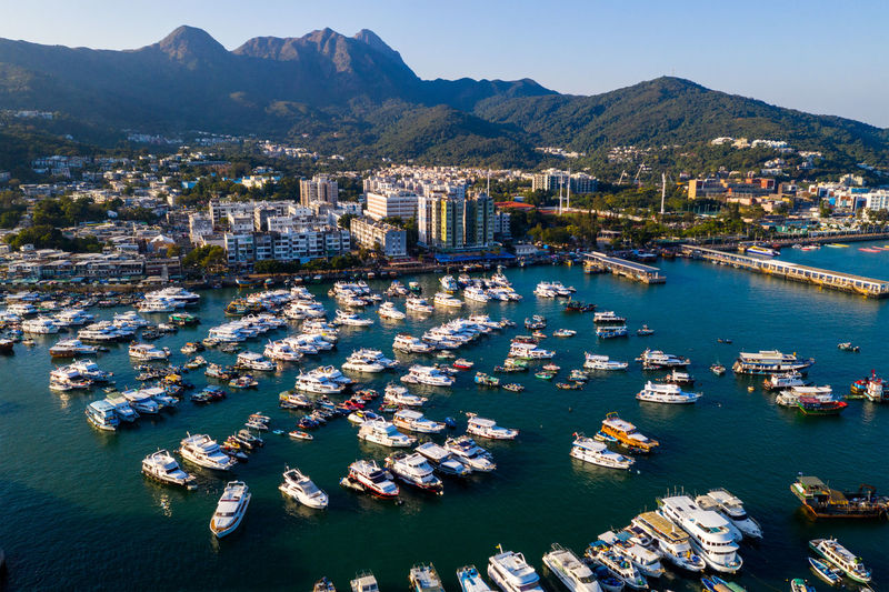 Aerial view of boats moored in sea by townscape