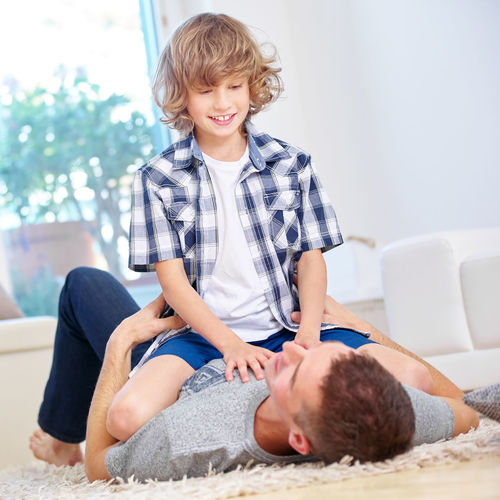 Smiling Son Sitting On Father At Home