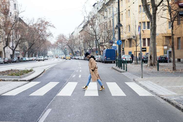 Side view of woman walking on road in city