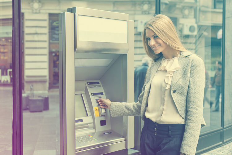 Portrait of young woman standing by atm machinery