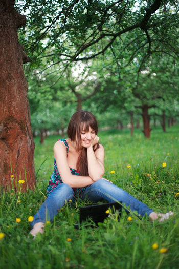 Full length of woman sitting on field