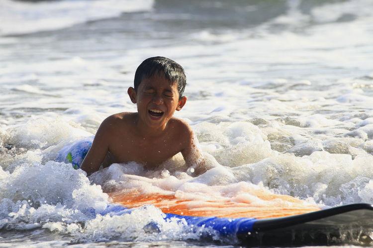 Portrait of shirtless boy in sea