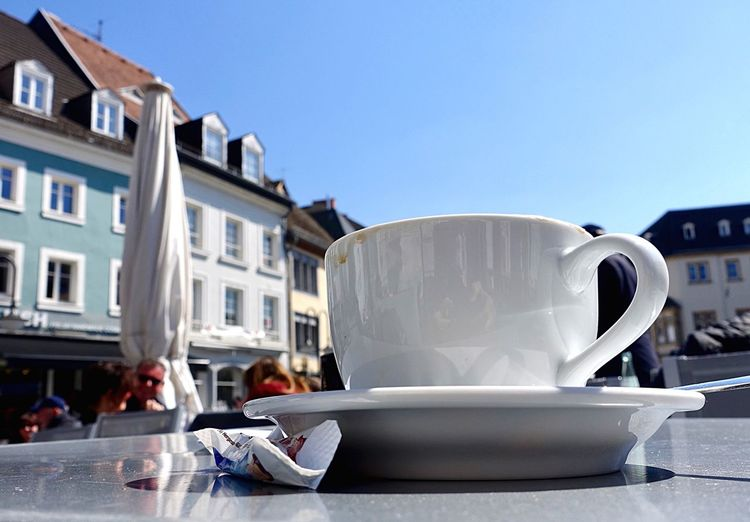 Close-up of coffee cup on table against sky