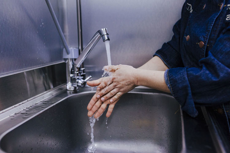 Midsection of woman washing hands in sink