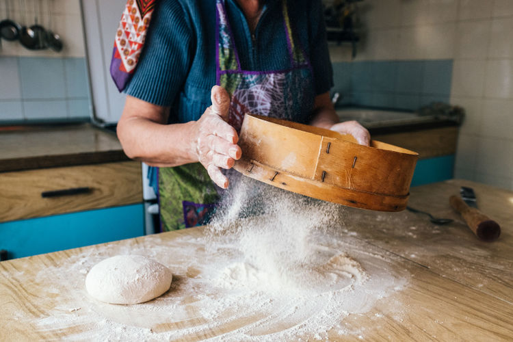 Midsection of woman sifting flour on table at home