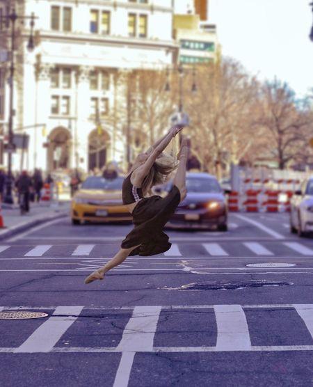 Full length of ballet dancer jumping on city street