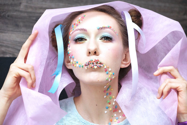 Portrait of woman wearing make-up with colorful candies
