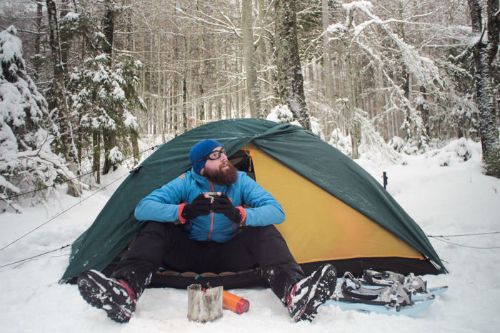winter camping on snow, hiker sitting in a tent having a cup of hot beverage Camping Cooking Expedition Exploring Freezing Hiking Man Stove Travel Trekking Winter Adult Adventure Clothing Cold Cold Temperature Day Forest Full Length Land Leisure Activity Male Men Nature Nutrition One Person Outdoors People person Shelter Sitting Snow Snowshoeing Snowshoes Survival Tent Trail Tree Warm Clothing Winter