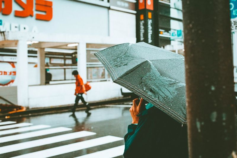 Side View Of Person With Umbrella Standing On Street During Rainfall