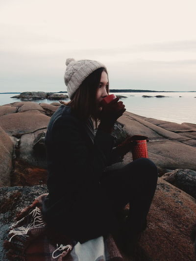 Young woman having drink while sitting on rock against sea