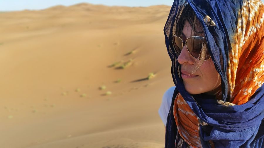 Portrait of woman wearing sunglasses on sand
